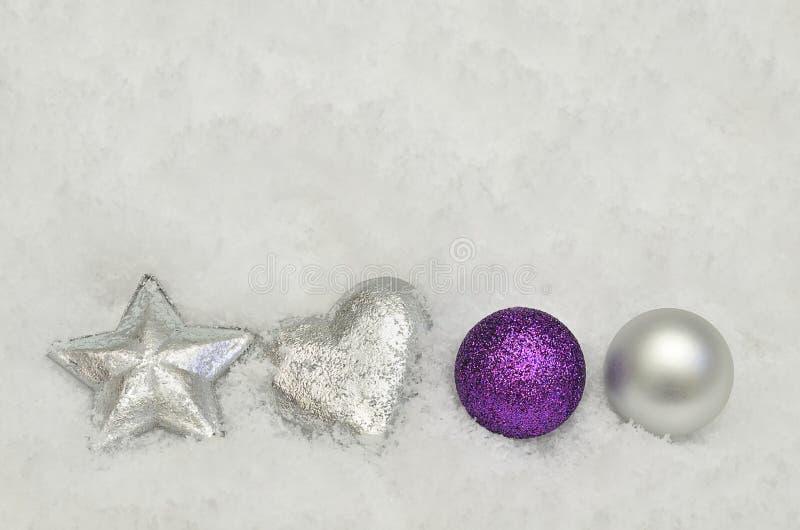Silberne und purpurrote Weihnachtsbaumdekorationen auf Schneehintergrund stockfoto