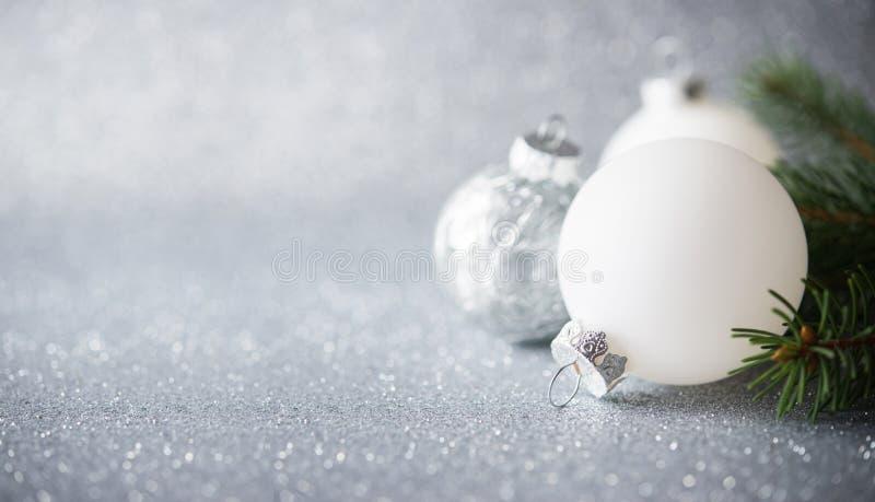 Silberne und weiße Weihnachtsverzierungen auf Funkelnfeiertagshintergrund Frohe Weihnacht-Karte lizenzfreie stockfotografie