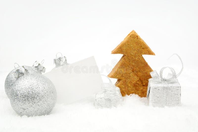 Silberne Weihnachtsdekoration auf Schnee mit Wunschkarte und -plätzchen lizenzfreies stockfoto