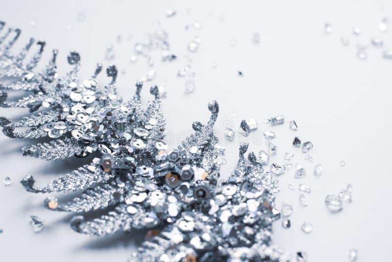 Silberne Weihnachtsdekoration in den Scheinen und im glänzenden zerbrochenen Glas auf einem weißen Hintergrund stockfoto