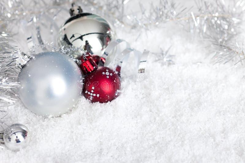 Silberne Weihnachtskugeln im Schnee stockbild