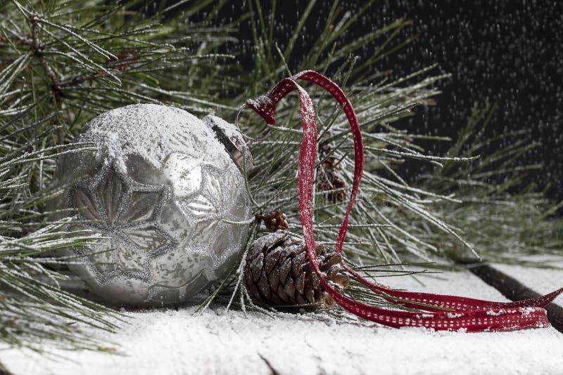 Silberne Weihnachtsverzierung im Schnee stockfotografie