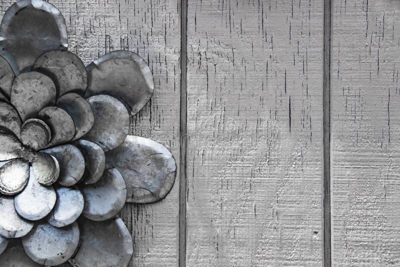 Silberner Hintergrund mit Metallblume auf rechter Seite gegen Silber malte raue hölzerne Planken stockfotos