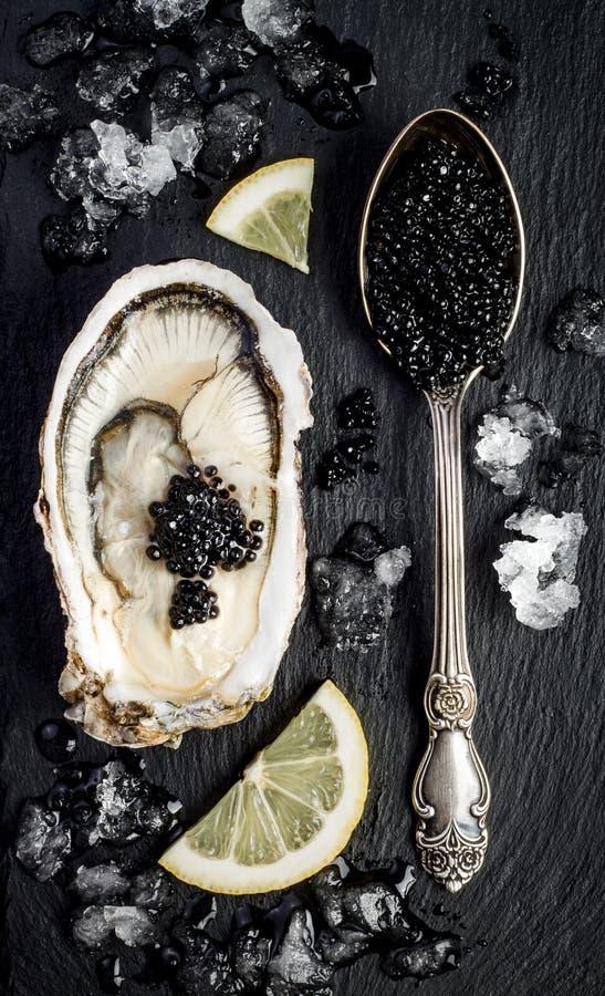 Silberner Löffel der Weinlese mit schwarzem Störkaviar und Auster auf schwarzem Schiefer entsteinen Hintergrund Draufsicht, flach lizenzfreie stockfotografie