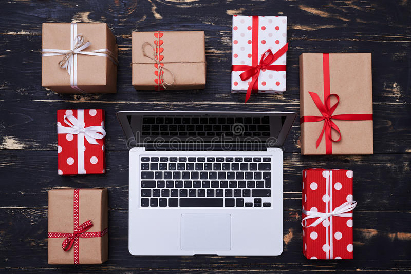Silberner Laptop umkreist mit vielen Geschenkboxen lizenzfreie stockfotos