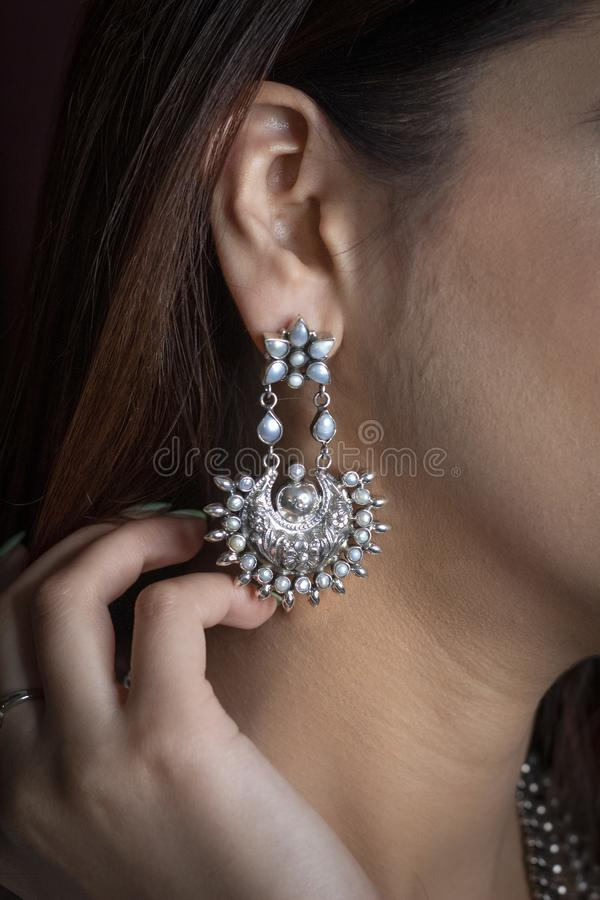 Silberner Ohrring auf Ohr einer Frau stockbilder
