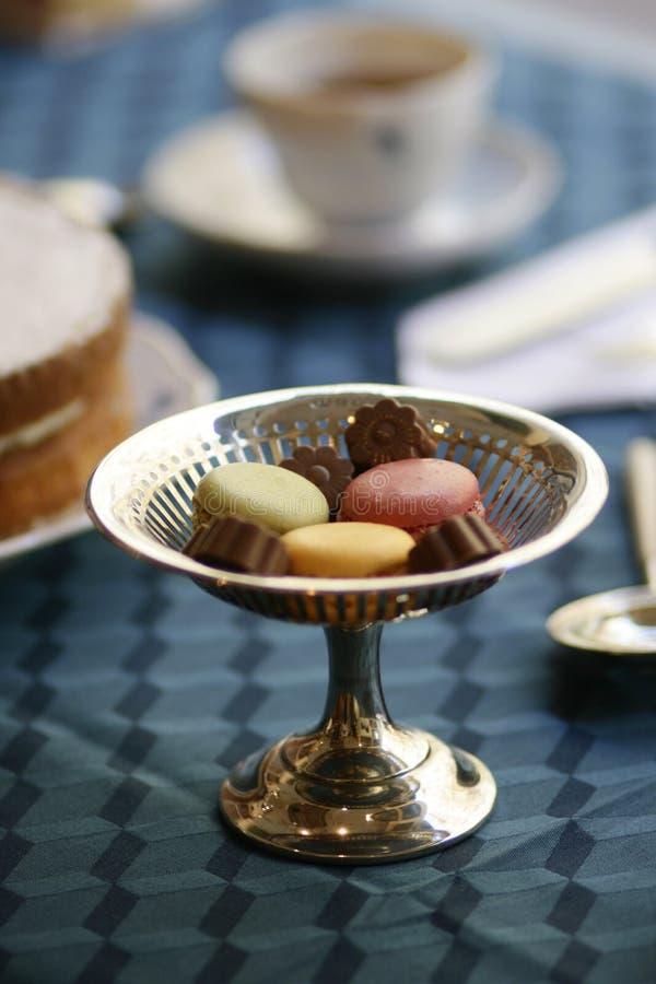 Silberner Süßigkeitssockel der Antiken mit Schokoladen und macarons stillife stockfotos