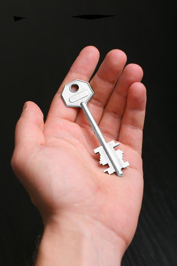 Silberner Schlüssel in der Hand lizenzfreie stockfotos