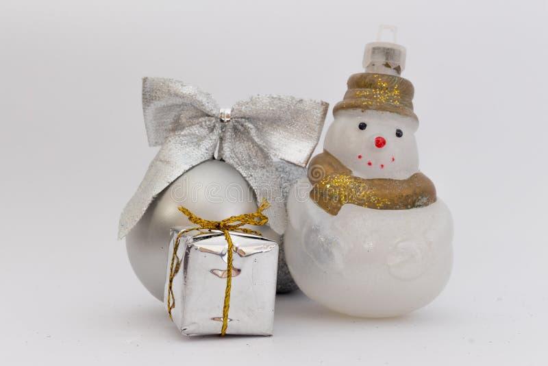 Silberner Weihnachtsball mit Schneemann und wenigem Geschenk auf weißem Hintergrund stockbild