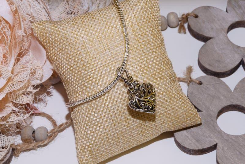 Silbernes Armband mit antikem Herzcharme stockfoto