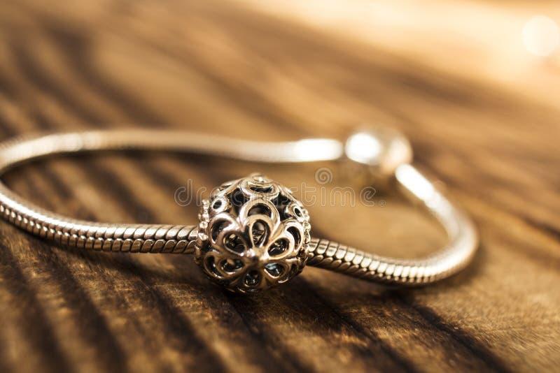 Silbernes Armband mit silberner Perle auf hölzernem Hintergrund stockbild