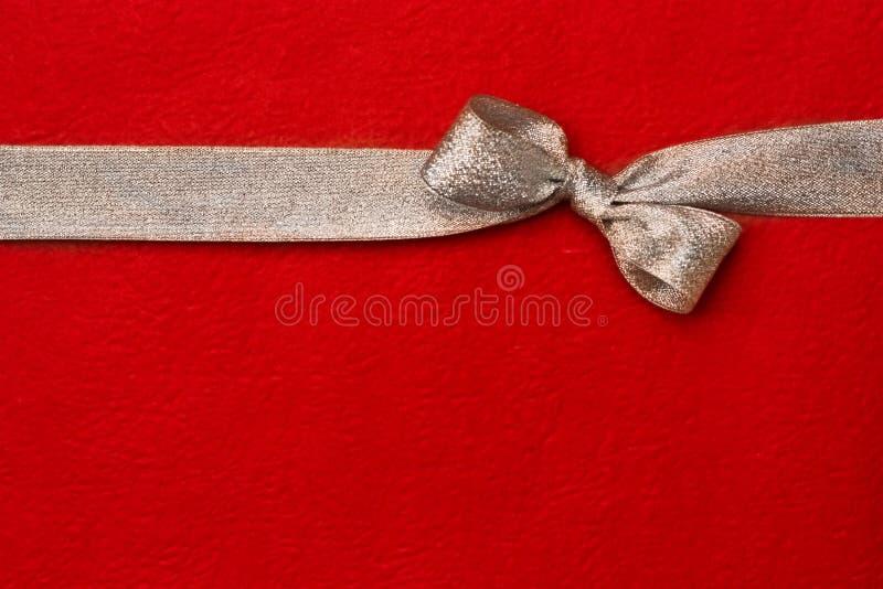 Silbernes Geschenkfarbband und -bogen auf rotem Hintergrund lizenzfreies stockbild