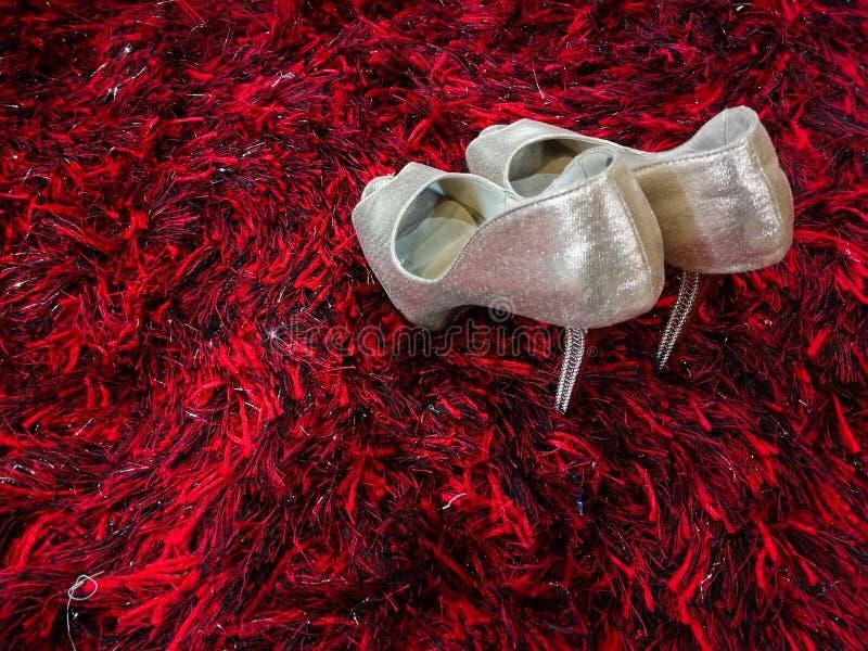 Silbernes glänzendes Stöckelschuhstilett auf rotem Teppich lizenzfreie stockfotos