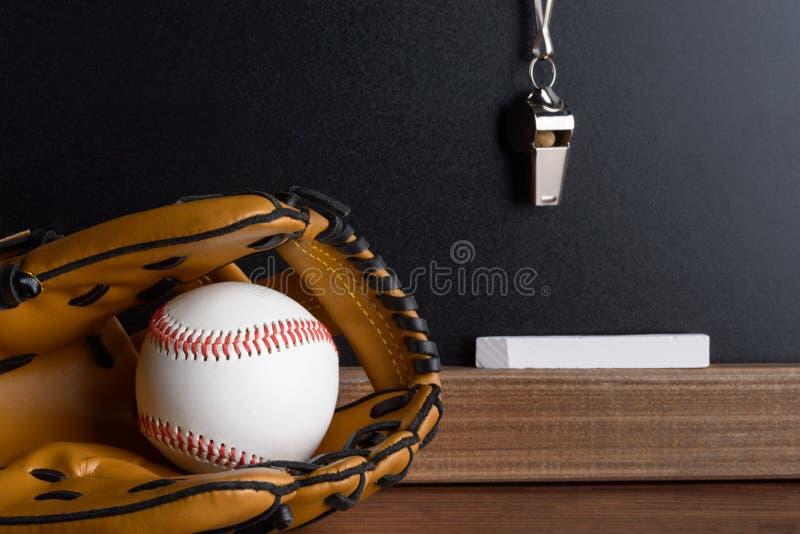 Silbido; tiza y guante de béisbol con la bola cerca de la pizarra fotos de archivo libres de regalías