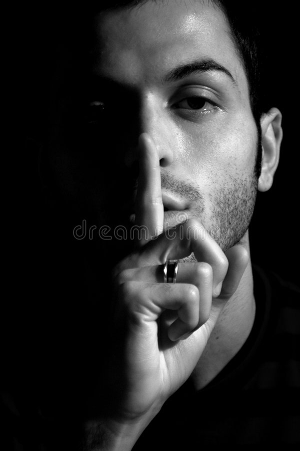 Silence Concept Man Shut Up. Expression of a man of the concept of silence / Shut up with his finger in front of his mouth and nose / Soft lights and black and stock photography