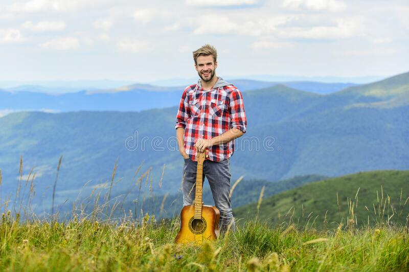 Silence of mountains and sound of guitar strings. Hipster musician. Inspiring environment. Man musician with guitar on. Top mountain. Inspired musician. Summer royalty free stock photos