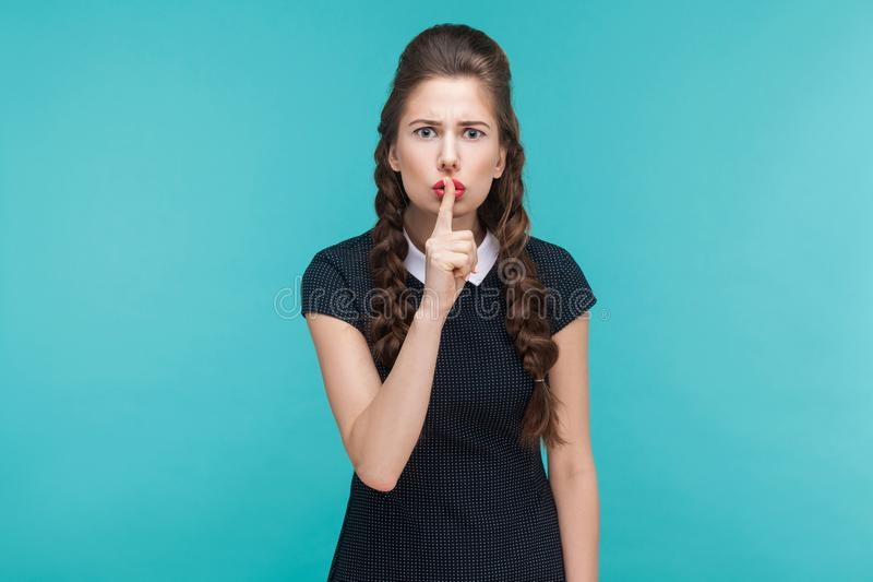 Silence, quiet, secret concept. Expressive young woman showing s. Hh sign. Indoor, studio shot on blue background stock photos
