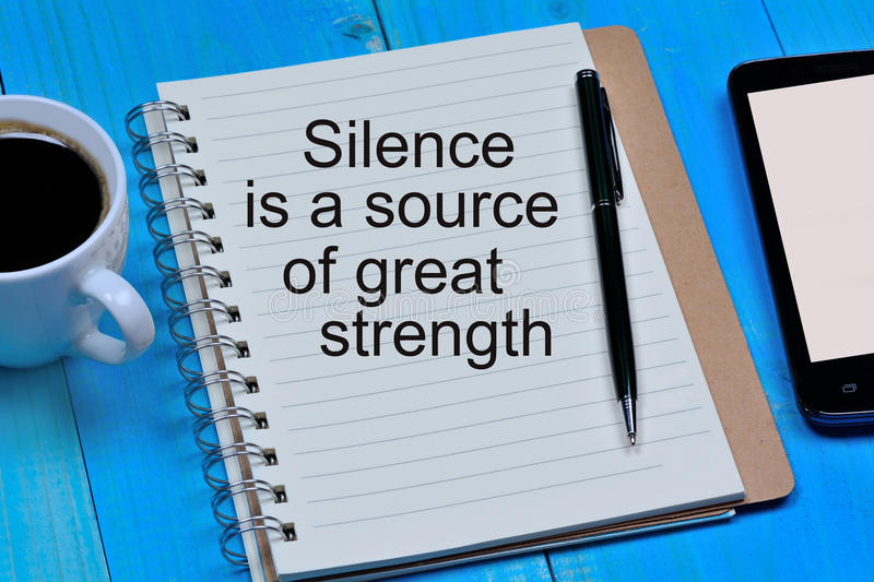 Silence is a source of great strength text on notebook royalty free stock photography