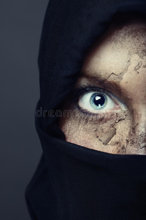 Silence of terror. Half face of the human in black hood with damaged skin. Artistic colors and painting added stock photo