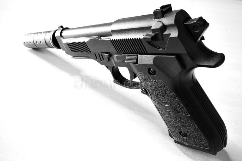 Silenced Pistol. A still life monochrome shot taken on a toy pistol with silencer mounted stock images