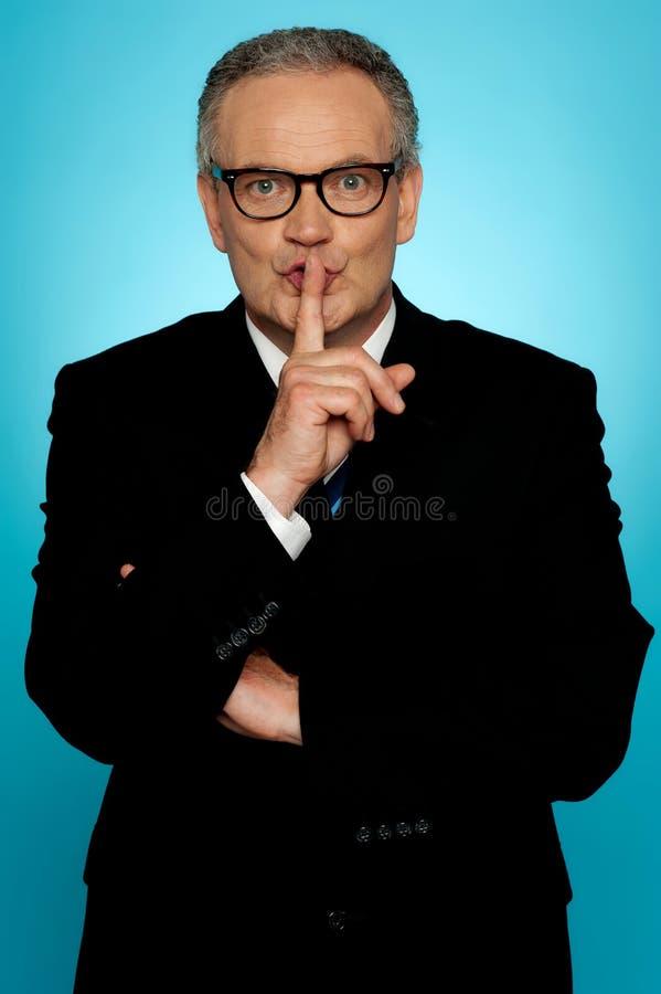 Silencio por favor, hombre de negocios que le mira foto de archivo libre de regalías