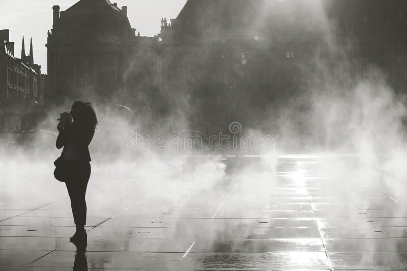Silhoette av kvinnan som tar bilden på vattenspegeln arkivfoto