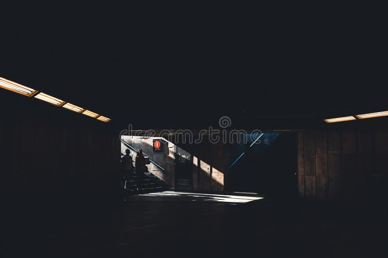 Silhoette of two people entering a dark shady underground building royalty free stock image