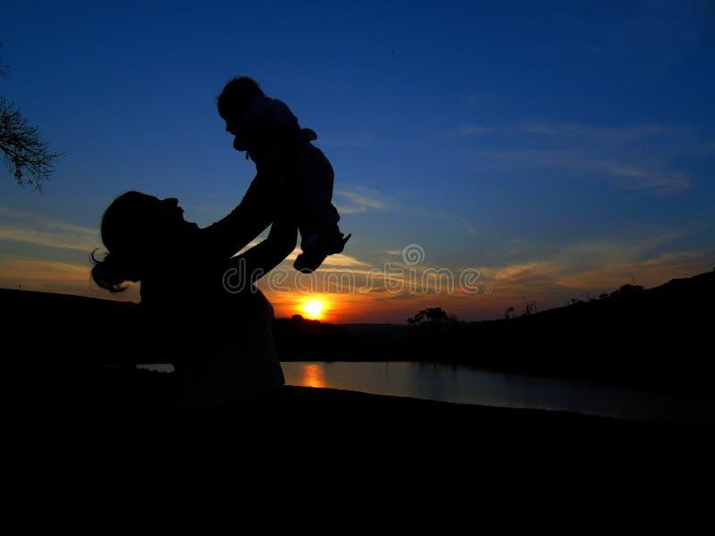 Silhoettesmoeder en baby op zonsondergang stock afbeeldingen