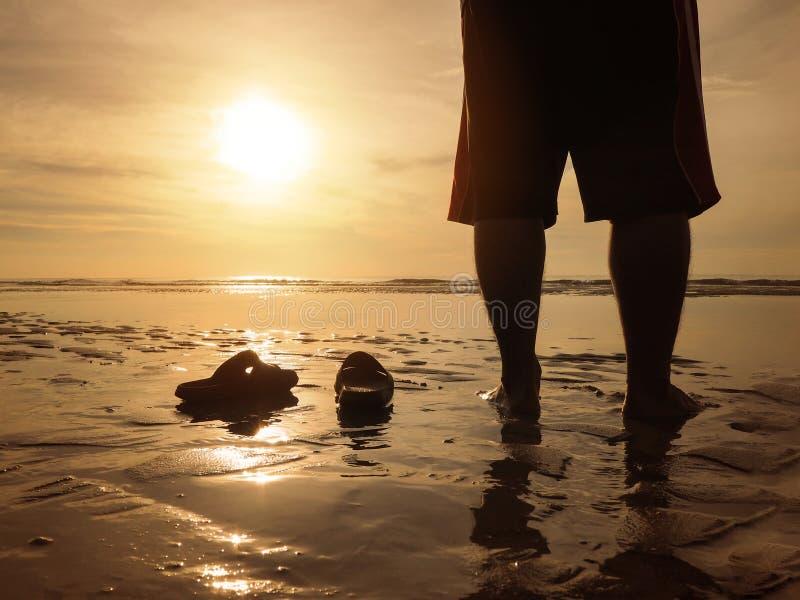 Silhouet achtermening die van de jonge mens zich bij gouden zonsondergangstrand bevinden met zijn sandals stock foto's