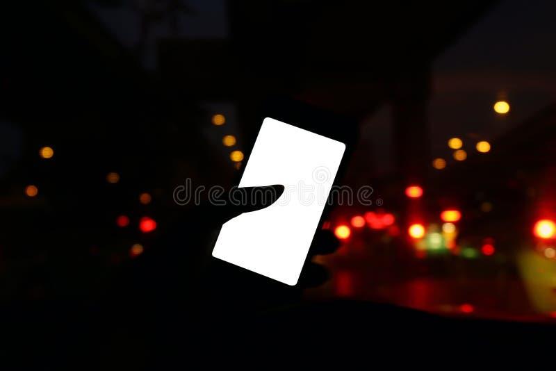 Silhouet in autonacht met frontale mening van moderne slimme telefoon en het lege witte scherm leeg voor exemplaarruimte voor uw  stock fotografie