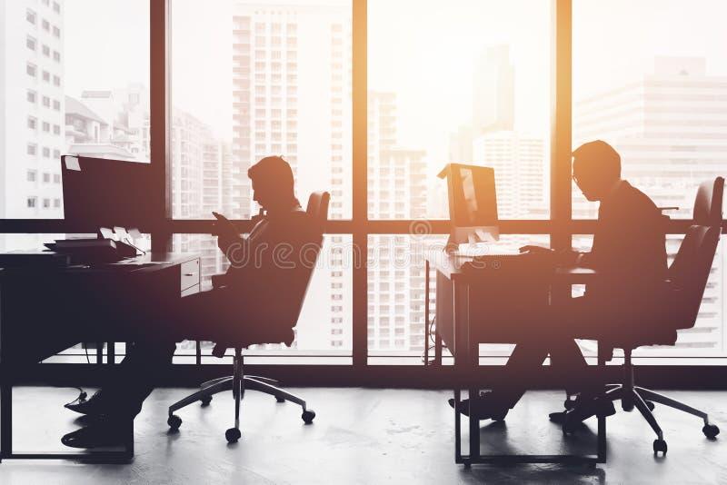 Silhouet bedrijfsmens in bureau die bij bureau werken stock foto