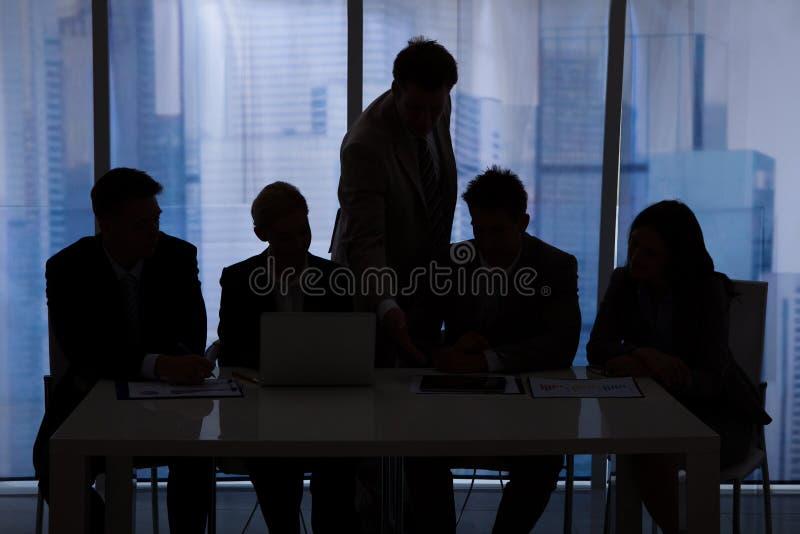 Silhouet bedrijfsmensen die in bureau bespreken royalty-vrije stock foto