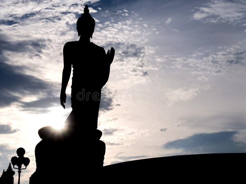 Silhouet die het standbeeld van Boedha met zonlichtgloed lopen royalty-vrije stock afbeeldingen