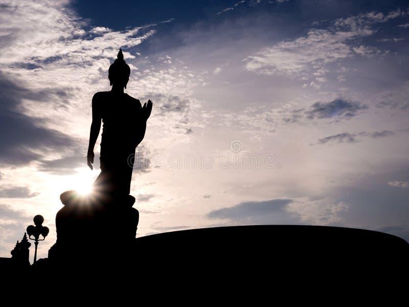 Silhouet die het standbeeld van Boedha met zonlichtgloed lopen royalty-vrije stock fotografie