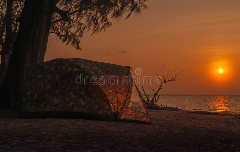 Silhouet die op het strand bij zonsondergang kamperen royalty-vrije stock afbeeldingen