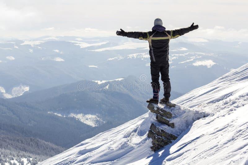 Silhouet die van alleen toerist zich op sneeuwbergbovenkant bevinden in wi royalty-vrije stock afbeelding