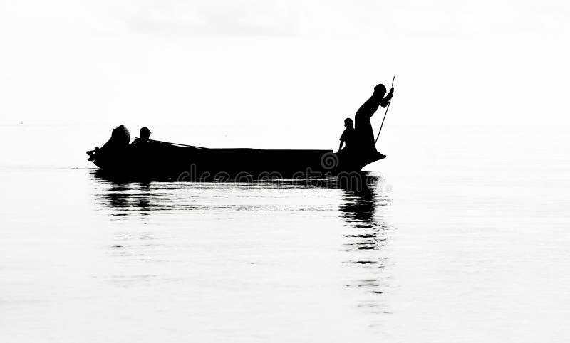 Silhouet die van dame tot stammen communautaire het roeien van Bajau boot in Semporna-Overzees, Sabah Semporna, Maleisië behoren royalty-vrije stock foto