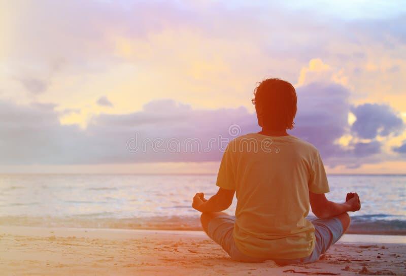 Silhouet die van de jonge mens bij zonsondergang mediteren royalty-vrije stock fotografie