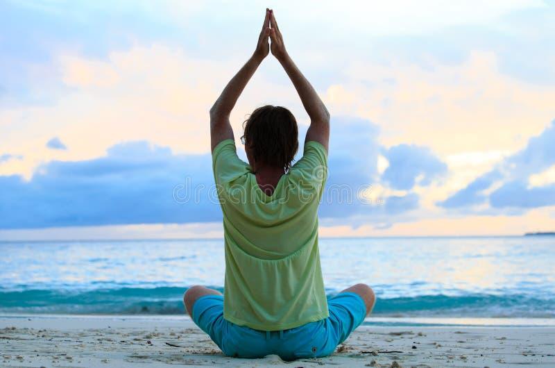 Silhouet die van de jonge mens bij zonsondergang mediteren stock afbeelding