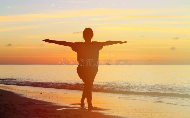 Silhouet die van de jonge mens bij zonsondergang mediteren royalty-vrije stock afbeeldingen