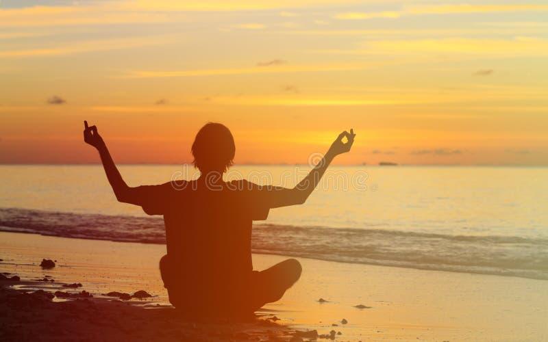 Silhouet die van de jonge mens bij zonsondergang mediteren stock foto