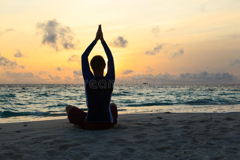 Silhouet die van de jonge mens yoga doen bij zonsondergang royalty-vrije stock afbeelding
