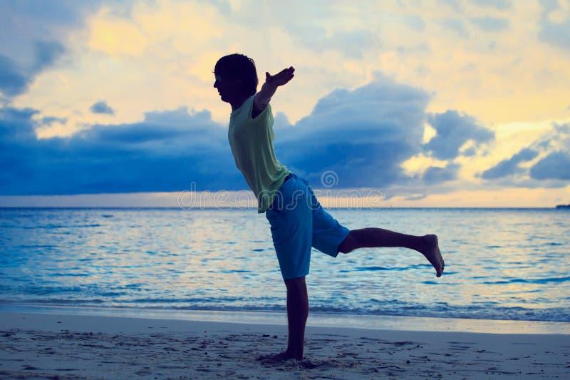 Silhouet die van de jonge mens yoga doen bij zonsondergang royalty-vrije stock foto