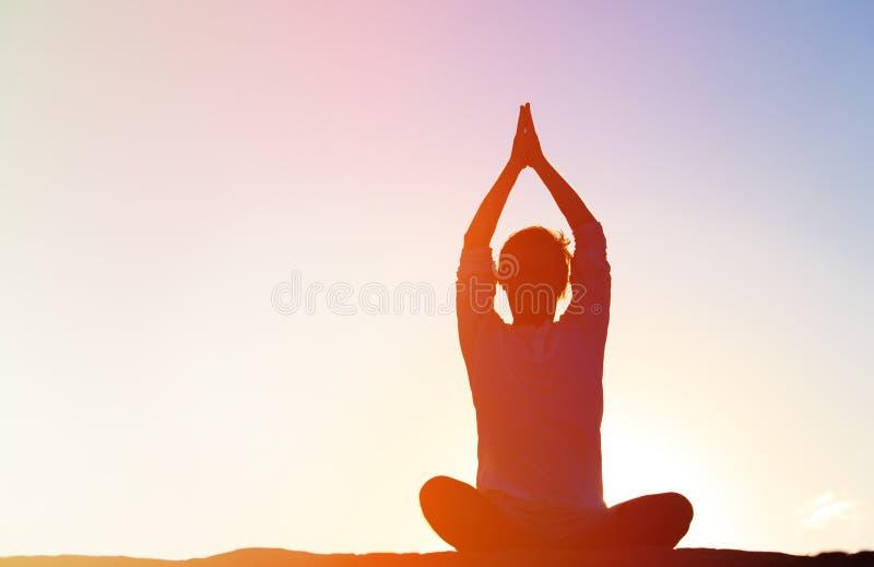 Silhouet die van de jonge mens yoga doen bij zonsondergang stock foto
