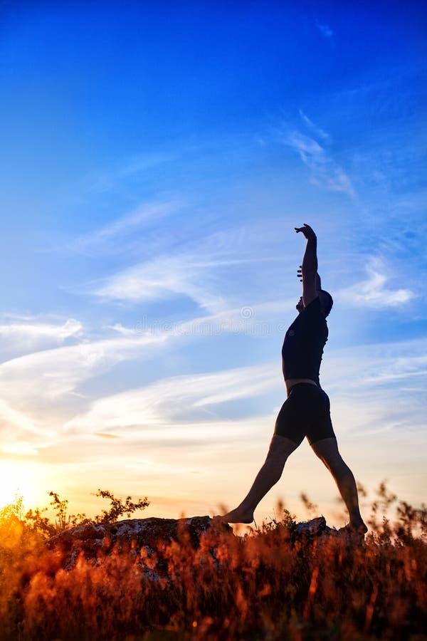 Silhouet die van de jonge mens yoga op de weide doen bij zonsondergang in het platteland royalty-vrije stock afbeelding