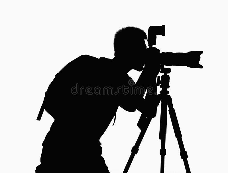 Silhouet die van de mens beelden met camera op driepoot nemen. stock foto