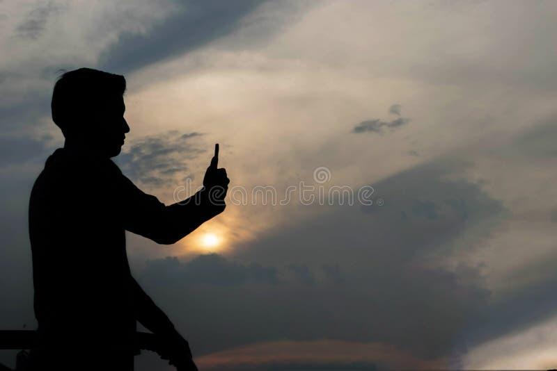 Silhouet die van de mens foto op smartphone nemen stock foto's