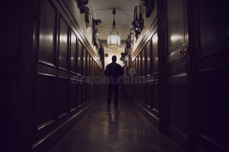 Silhouet die van de mens zich in donkere gang in een oud huis bevinden stock afbeelding