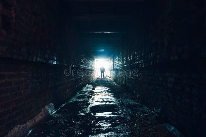 Silhouet die van de mens zich in donkere ondergrondse gang bevinden Licht op eind van tunnelconcept stock foto