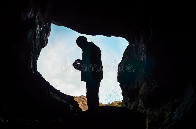Silhouet die van de mens zich in een donker hol bevinden royalty-vrije stock afbeeldingen